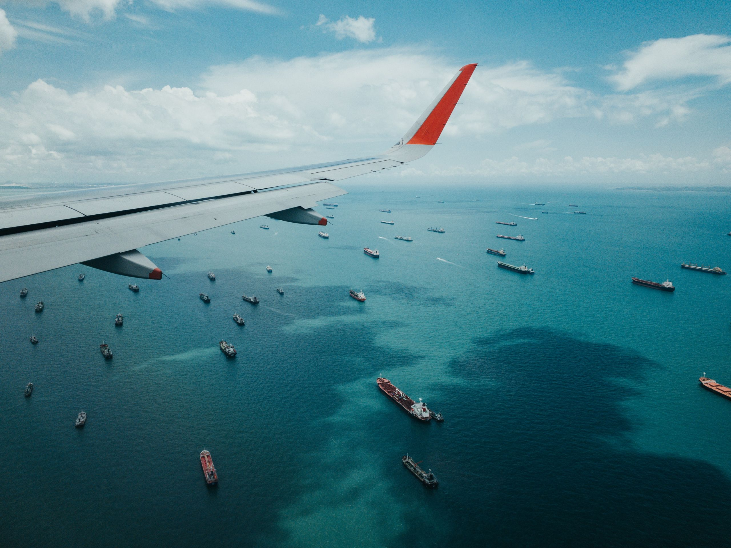 aeroplane flying above many shipping vessels